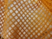 Close up of the commercial grade polyester material of our orange mesh laundry bag.